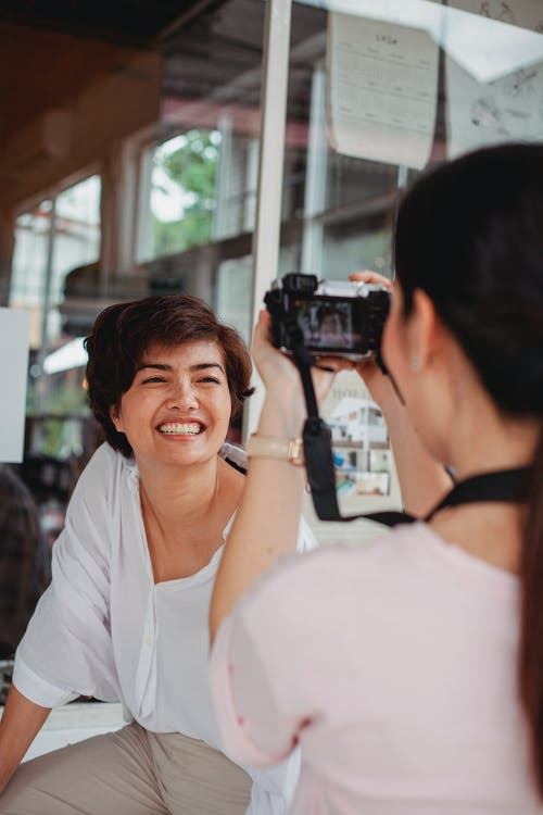 Anonymous woman taking photo of positive ethnic girlfriend on camera