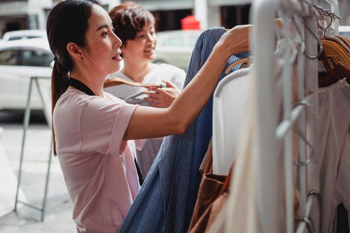 Asian buyers choosing clothes on rack in street shop