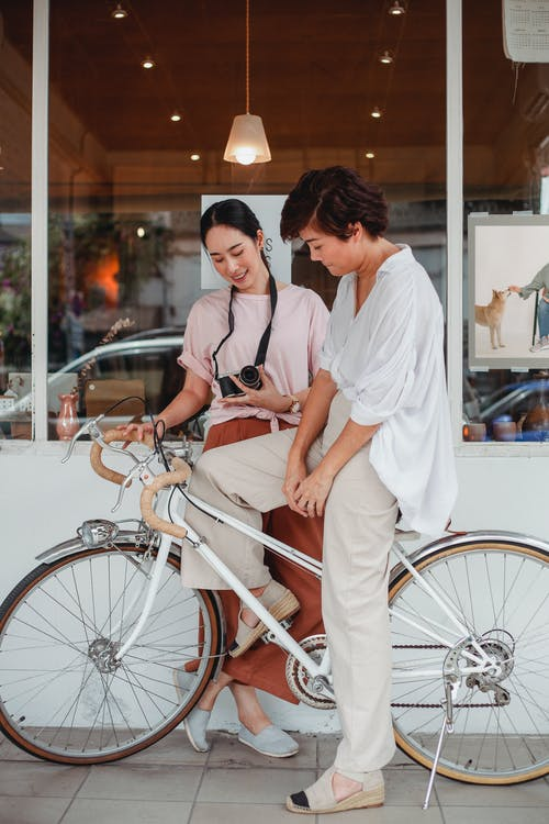 Man and Woman Standing Beside Bicycle