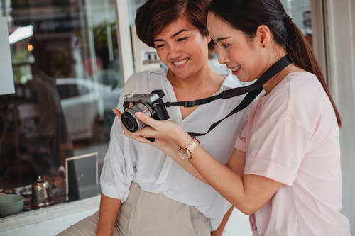 Crop happy Asian girlfriends sharing photo camera on city street
