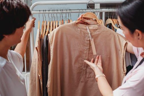 Обрезайте азиатских покупателей, которые выбирают одежду в магазине