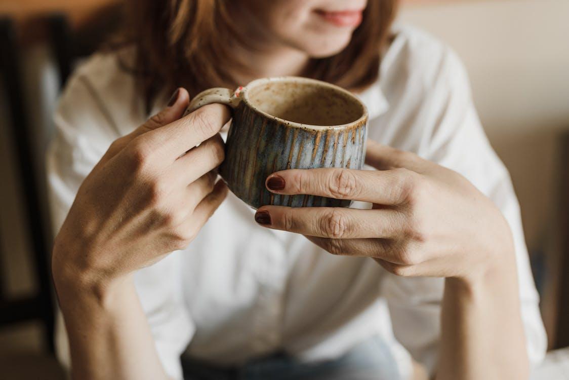 Woman in White Long Sleeve Shirt Holding Brown Ceramic Mug