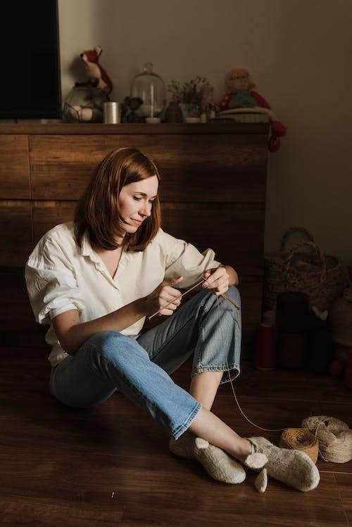 Wanita Berkemeja Putih Dan Jeans Denim Biru Duduk Di Lantai
