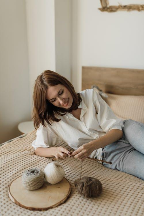 白色長袖襯衫和灰色的褲子,坐在棕色的沙發上的女人