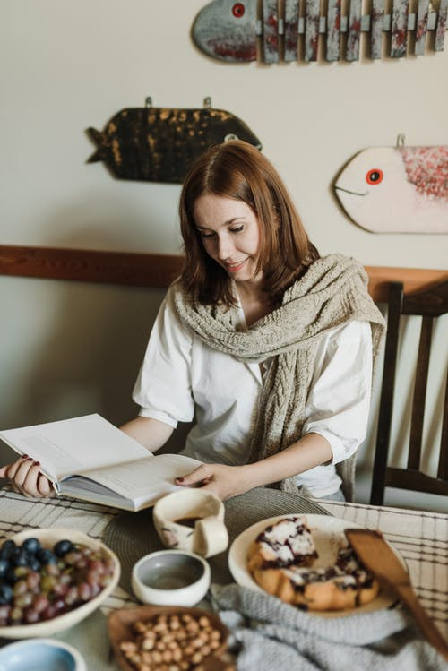 Smiling woman reading book while sitting at table with dessert