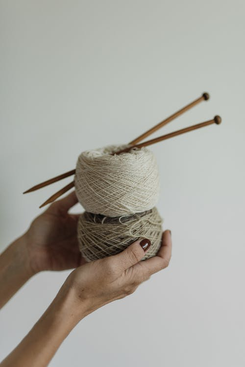 A Person Holding a Thread with Knitting Pins