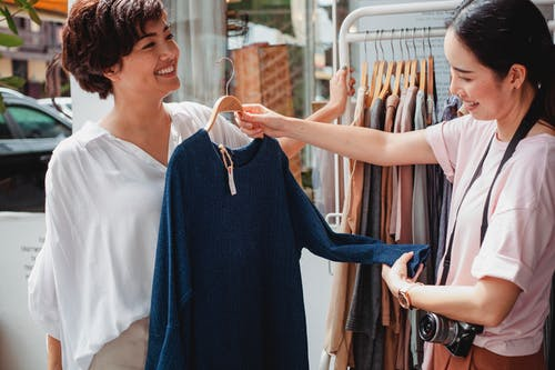 Crop Asian buyer with girlfriend selecting clothes in street shop