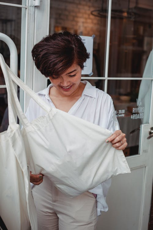 Young glad ethnic buyer watching white fabric bag near glass door in street shop