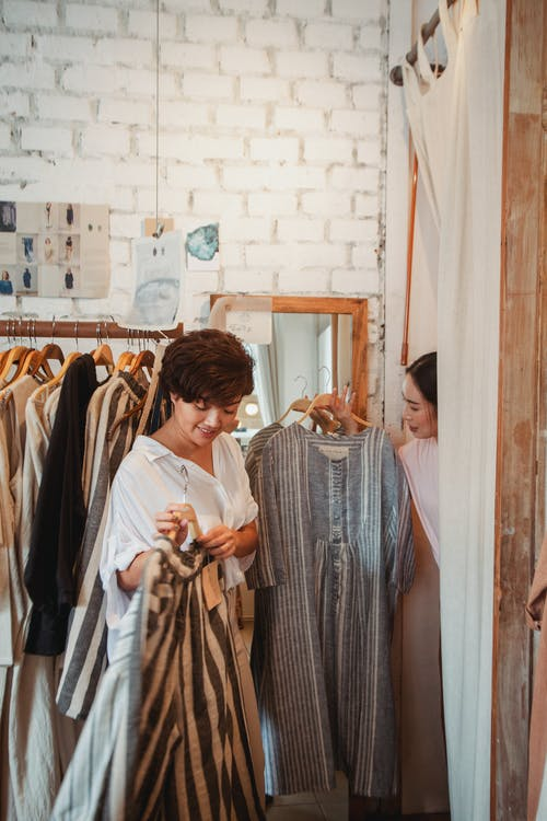 Stylish young ethnic female customers exploring new collection of fashion boutique