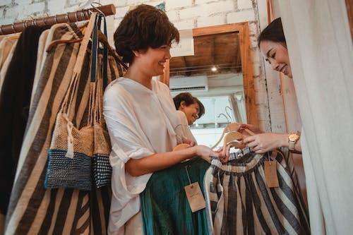 Conteúdo, Jovens Mulheres Viciadas Em Compras étnicas Escolhendo Roupas Em Boutique