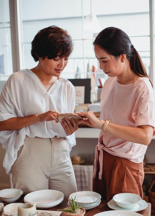 Modieuze Jonge Aziatische Vrouwen Die Keukengerei In Opslag Kiezen