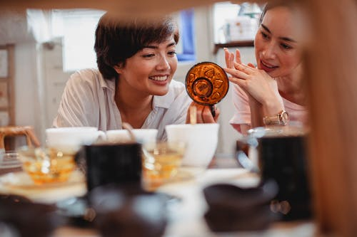 Crop positive ethnic females examining creative glass teacup standing near table with collection of various dishware in store