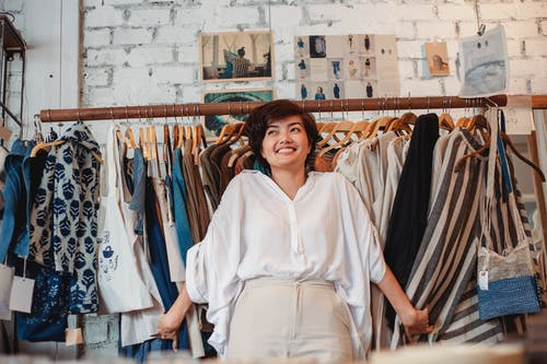 Cheerful young ethnic lady smiling while holding stack of clothes hanging on rack