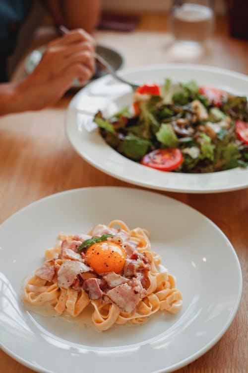 不可識別的人在餐廳的午餐時間吃沙拉和意大利細麵條