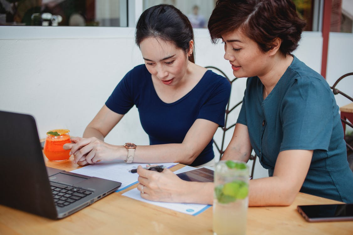 Concentrated female entrepreneurs in casual clothes sitting at table with gadgets and cocktails while signing documents