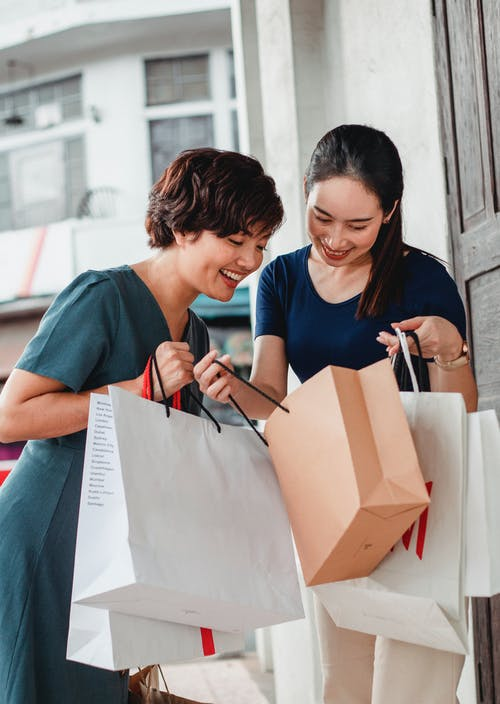 Ethnic female friends in casual clothes holding shopping bags and looking at goods while standing on street and smiling