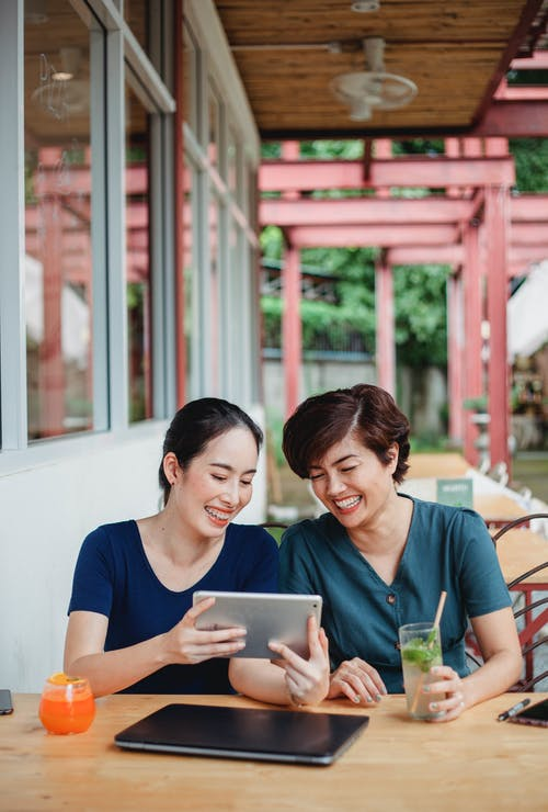 Laughing Asian girlfriends with gadgets and cocktails