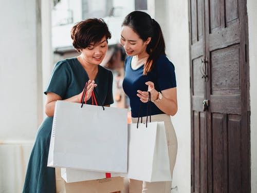 Happy ethnic women holding paper bags after shopping and showing purchases to each other