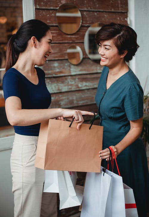 Happy women with paper shopping bags