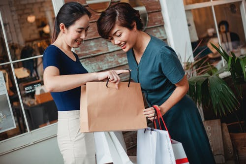 Happy Asian woman showing purchase to girlfriend