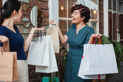 Laughing Asian female with shopping paper bags toothy smiling while standing with girlfriend near entrance of building