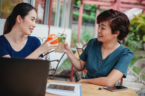 Cheerful Asian businesswomen with cocktails after successful deal