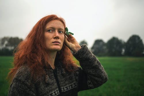 Pensive redhead woman decorating hair with flower in nature