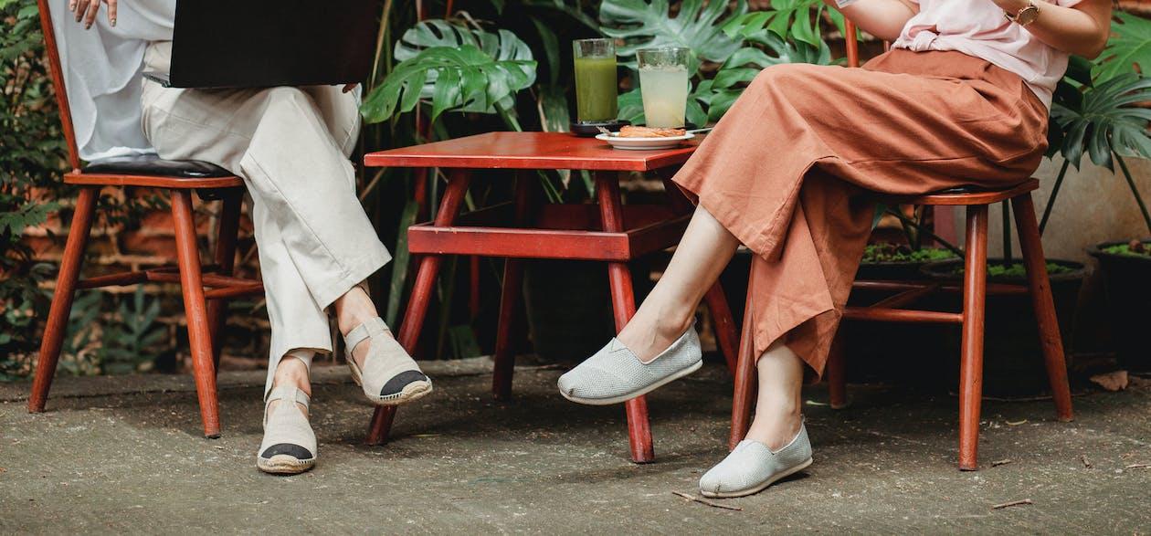 Crop stylish women on terrace of cafe