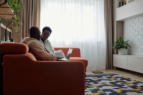 Man in White Shirt Sitting on Orange Sofa Chair
