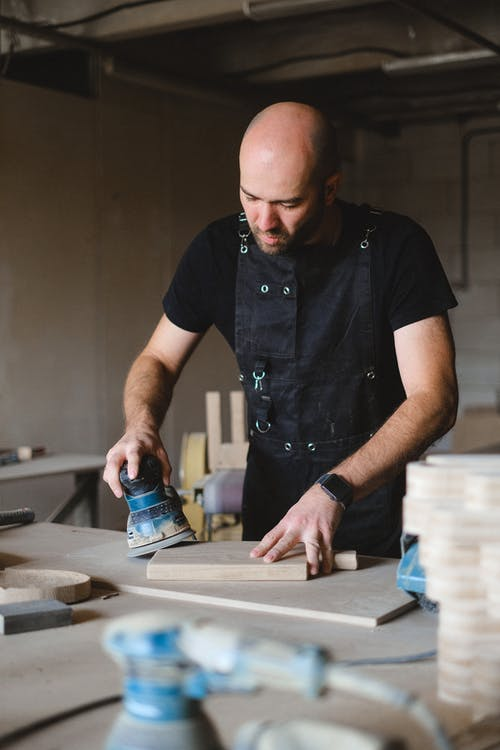 Concentrated bald male woodworker wearing black apron polishing wooden board with special instrument while working at workbench in professional joinery