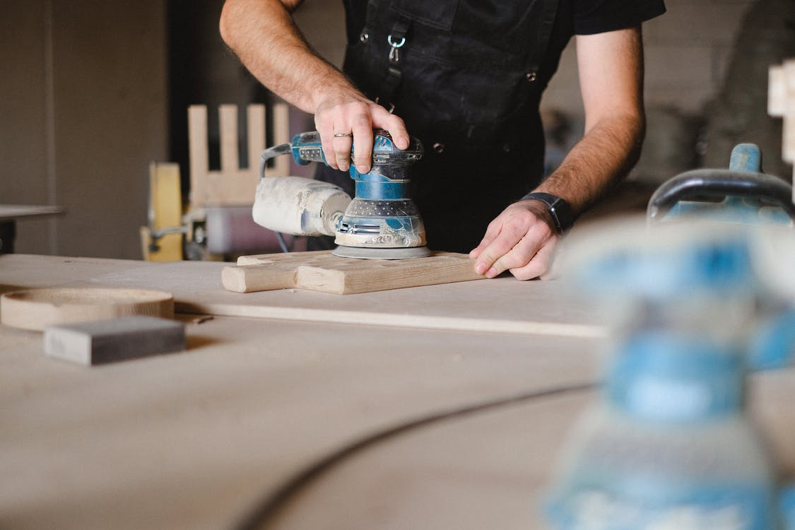 Unrecognizable male woodworker wearing uniform and polishing wooden board with random orbital sander at big table in professional studio