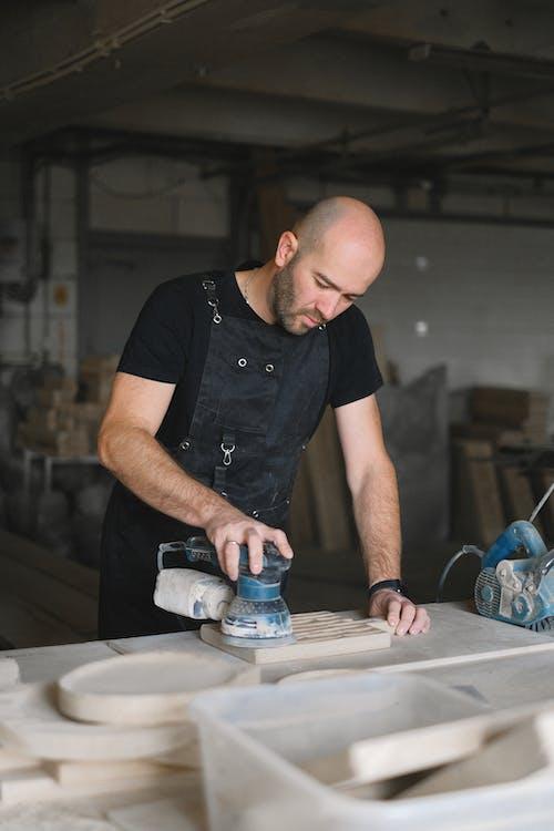 Focused artisan polishing wooden plank