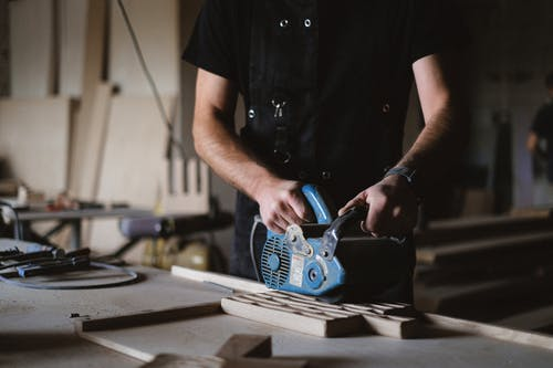 Crop craftsman polishing wooden board