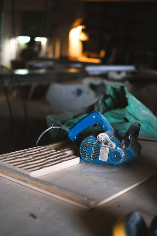Blue electrical special tool for wood polishing placed on workbench with wooden board in professional joinery with equipment on blurred background