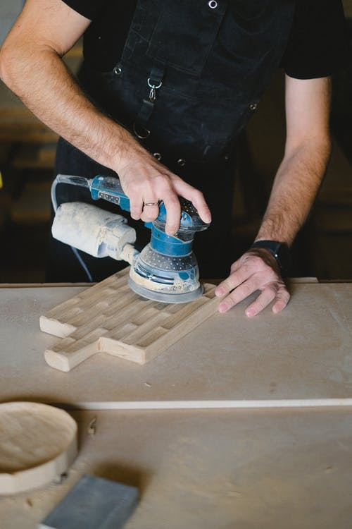 Crop carpenter using sander in workshop