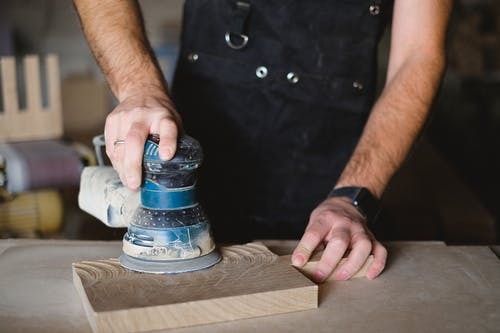 Unrecognizable male carpenter using random orbital sander while working with wooden detail at workbench in professional workshop  on blurred background