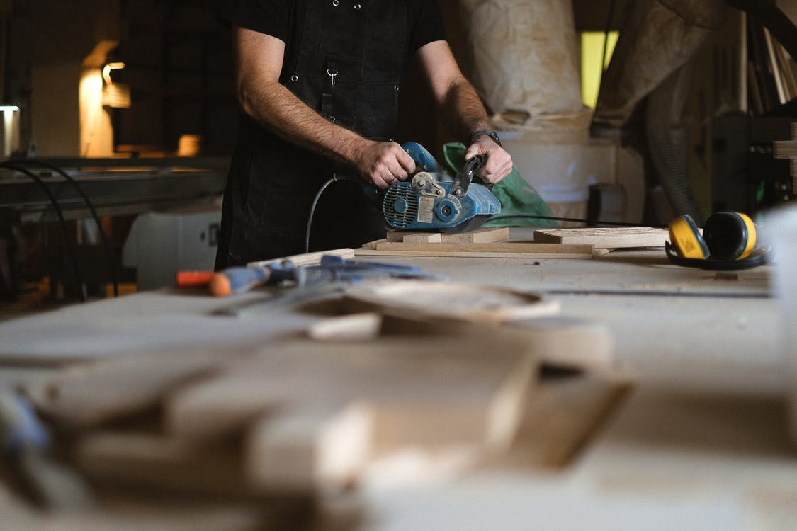 Unrecognizable male artisan using electric belt sander while working at workbench with blurred stack of wooden planks in professional joinery