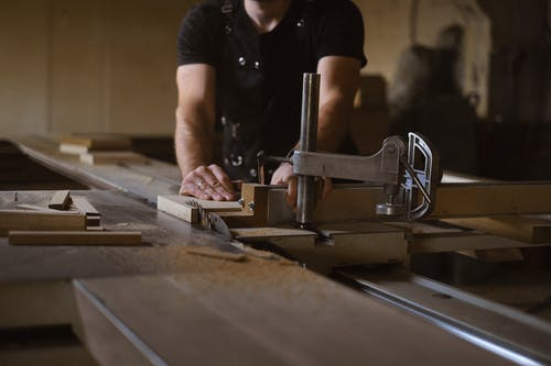 Anonymous male woodworker in apron standing at sawbench while working with wooden details in professional carpentry with stack of wood