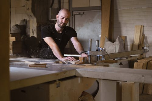 Focused craftsman working with table saw