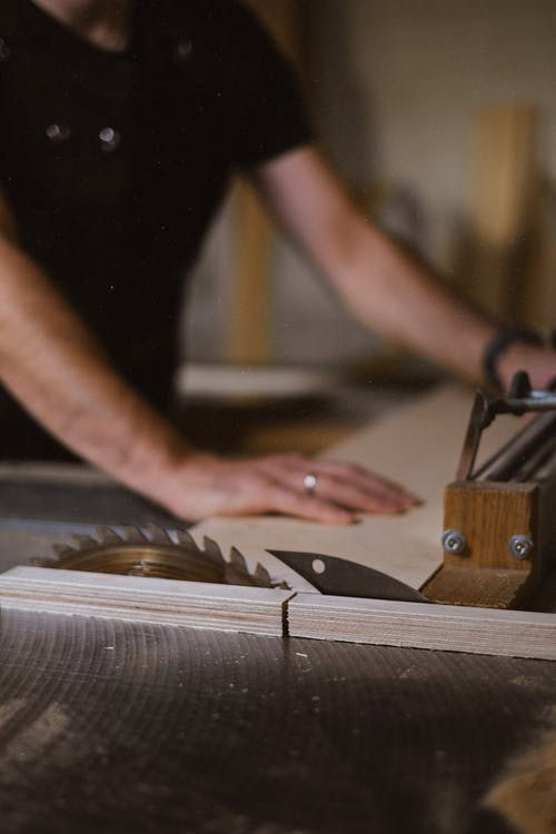 Unrecognizable blurred male master cutting wooden plank using table saw with sharp knives while working in professional workshop with special instruments