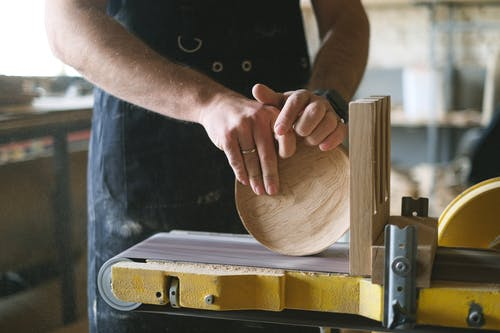 Unrecognizable male woodworker shaping round wooden detail while working at belt and disc sander in professional workshop on blurred background
