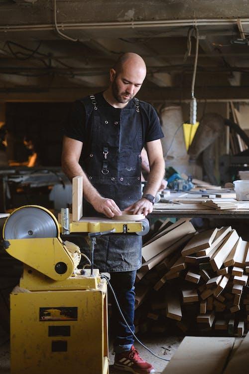 Skilled joiner using electric belt and disc sander