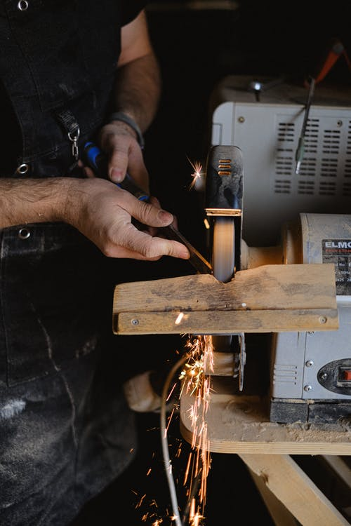 Unrecognizable male master in apron using special machine to sharpen wooden detail while working in professional joinery with special instrument