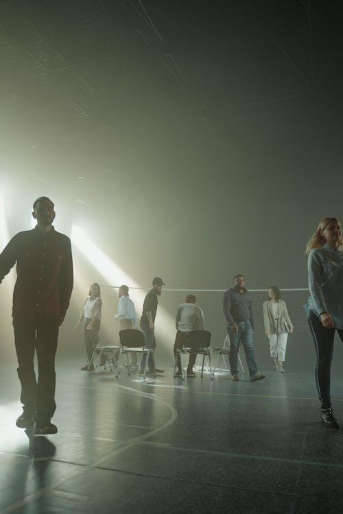 Man in Black Jacket Standing Beside Woman in Blue Denim Jeans