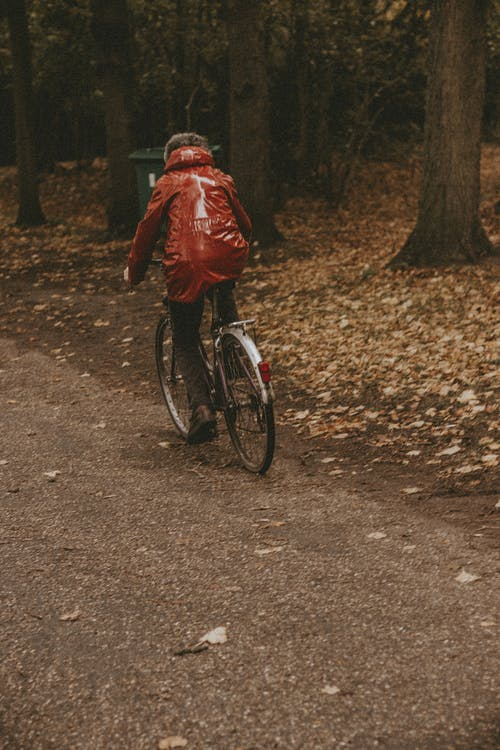 Man in Red Jacket Riding Bicycle on Dirt Road