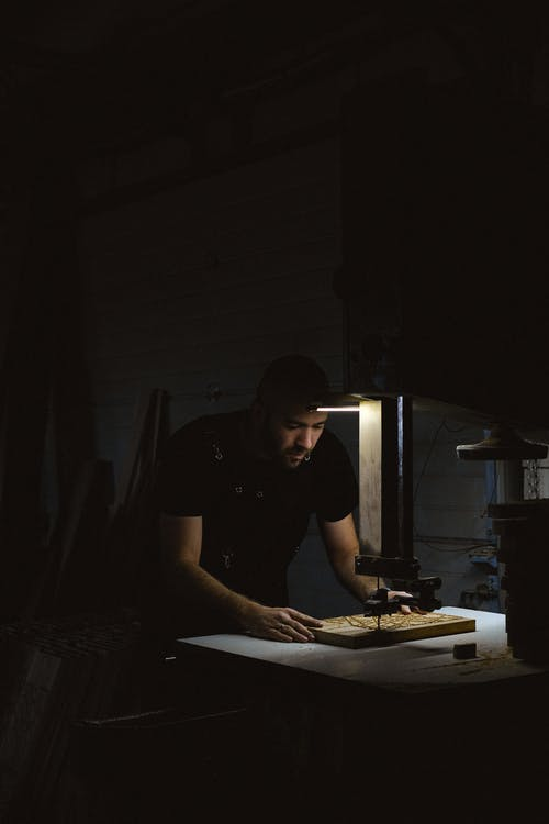 Focused craftsman working with wooden details at workbench