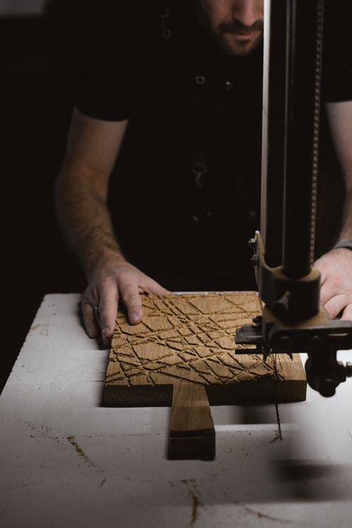Unrecognizable male master standing at workbench with metal industrial bandsaw machine while working with wooden plank in professional joinery in darkness
