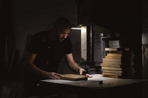 Focused craftsman carving wooden board