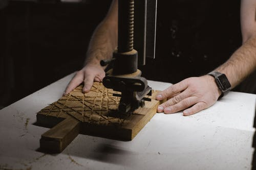 Unrecognizable male carpenter using special metal instrument to carve wooden board while working at workbench on black background in dark workshop
