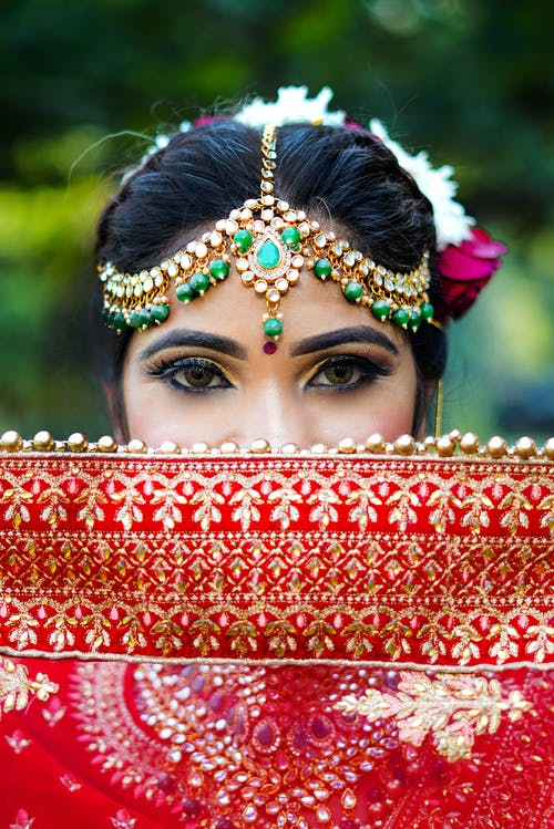Woman With Makeup and Head Accessories Behind Red Scarf